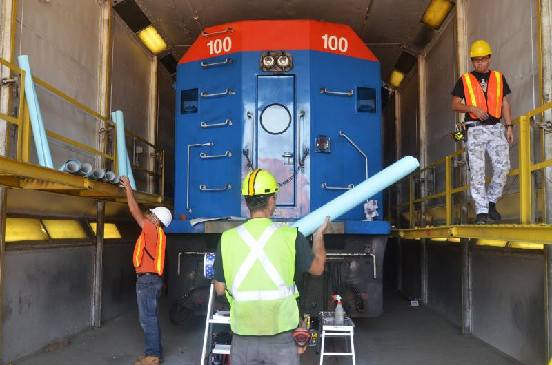 Vinyl rolls are organized and placed on their respective sides of the locomotive.